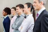 Smiling Customer Service Representative Standing With Colleagues — Stock Photo