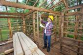 Worker Taking Measurements In Timber Cabin — Stock Photo