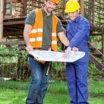 Confident Architect With Colleague Explaining Blueprint At Site — Stock Photo #70264161