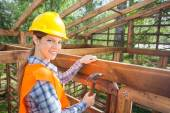 Happy Female Worker Hammering Nail On Timber Frame — Stock Photo