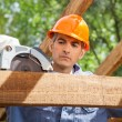 Construction Worker Using Electric Saw On Timber Frame — Stock Photo #70357161
