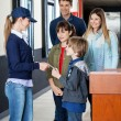 Family Giving Ticket To Worker For Examination At Cinema — Stock Photo #70358213