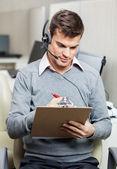 Customer Service Representative Writing On Notepad — Stock Photo