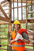 Happy Worker Holding Pipe In Incomplete Wooden Cabin — Stockfoto