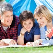 Family Looking At Map In Tent — Stock Photo #70962701