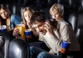 Family Looking At Man Using Mobilephone In Theater — Stock Photo