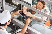 Cliente pagar a través de Smartphone en la tienda de carniceros — Foto de Stock