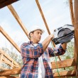 Construction Worker Using Electric Saw On Timber Frame At Site — Stock Photo #72036819