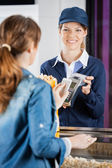 Concession Worker Accepting Payment From Woman Through NFC Techn — Stock Photo