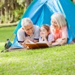 Grandparents Reading Book For Granddaughter At Campsite — Stock Photo #74975995