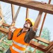 Construction Worker Cutting Wood With Handsaw At Site — Stock Photo #74978715