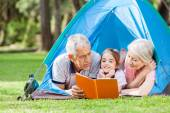 Grandparents With Granddaughter Reading Book In Tent — Stock Photo
