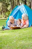 Grandparents Reading Book For Granddaughter At Campsite — Stock Photo