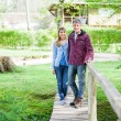 Couple Walking On Wooden Bridge — Stock Photo #74981195