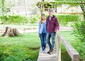 Couple Walking On Wooden Bridge — Stock Photo