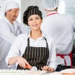 Happy Chef Cutting Ravioli Pasta With Colleagues In Background — Stock Photo #76278813