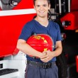 Happy Firefighter Holding Helmet At Fire Station — Stock Photo #80164932