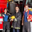 Confident Young Firefighters Standing Against Trucks — Stock Photo #80166668