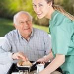 Portrait Of Smiling Female Nurse Serving Breakfast To Senior Man — Stock Photo #80171734