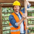 Portrait Of Construction Worker Measuring Timber Frame — Stock Photo #80554812