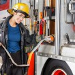Portrait Of Happy Firefighter Adjusting Hose In Truck — Stock Photo #80593330