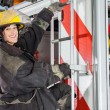 Smiling Firefighter Standing On Truck At Fire Station — Stock Photo #80600878