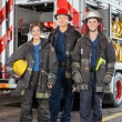 Portrait Of Confident Firefighters Standing Against Truck — Stock Photo #80603034