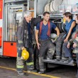Постер, плакат: Firefighters Conversing By Firetruck