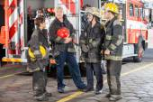 Portrait Of Confident Firefighter Standing With Team — Stock Photo