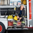 Confident Fireman Sitting In Truck At Fire Station — Stock Photo #81021022