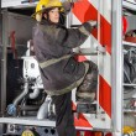 Firewoman Climbing Truck At Fire Station — Stock Photo #81025272