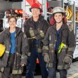 Happy Firefighters Standing Against Truck — Stock Photo #81025348