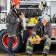 Firefighters Discussing By Truck At Fire Station — Stock Photo #81144978