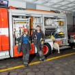 Firefighters Leaning On Truck At Fire Station — Stock Photo #81145990