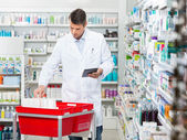 Farmacista conteggio Stock mentre che tiene compressa digitale In Drugst — Foto Stock