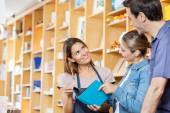 Happy Saleswoman Showing Book To Customers — Stock Photo
