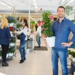 Confident Man Holding Flower Plant In Shop — Stock Photo #82003498