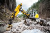 Wheeled excavator in a river in the autumn forest mountains — Stock Photo
