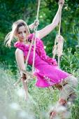 Beautiful young woman on a swing — Stock Photo