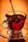 Tea pouring into glass cup — Stock Photo
