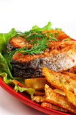 Fried fish with potato chips and greenery — Photo