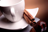 Tea cup with cinnamon and chocolate candy — ストック写真