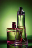 Perfume bottles isolated on green — 图库照片