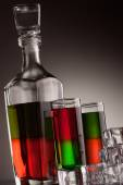 Carafe and glasses filled with multicoloured alcohol drinks — Stock Photo