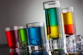 Glasses filled with multicoloured alcohol drinks — Stock Photo