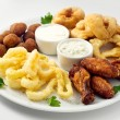 The beer plate with spicy chicken wings, calamari rings, fries onion rings, cheese balls, breaded, tartar sauce and garlic — Stock Photo #58182869