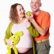 The pregnant woman with her husband with green apple — Stock Photo #63799917