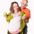 The pregnant woman with her husband with green apple — Stock Photo #63799983