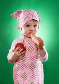 The baby girl with a kerchief and kitchen apron holding an vegetable isolated — Stock Photo