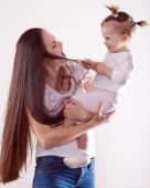 La joven madre con cabello largo castaño en jeans sosteniendo un bebé — Foto de Stock